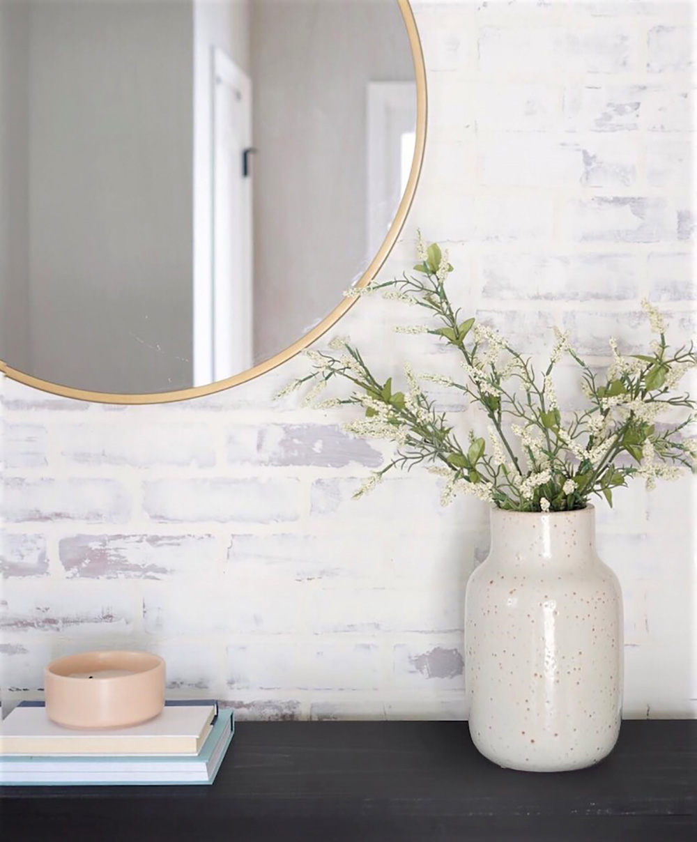 A decorative vase with greenery sits on a table in front of a faux whitewashed brick accent wall.