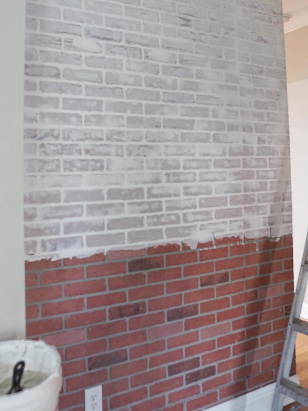 A partially faux whitewashed brick accent wall.