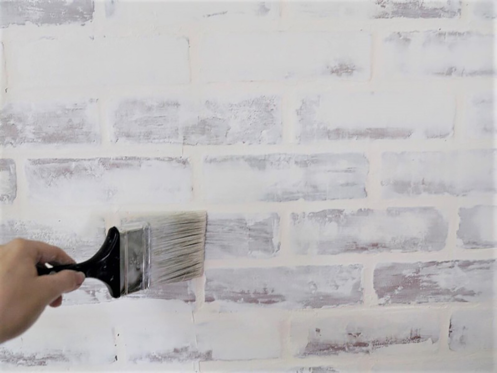 A person sealing a faux whitewashed brick accent wall.