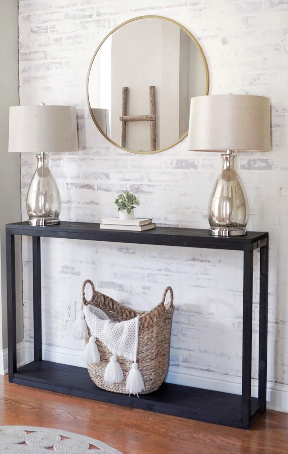 An updated entryway with a DIY faux whitewashed brick accent wall behind a table with two lamps and a mirror.