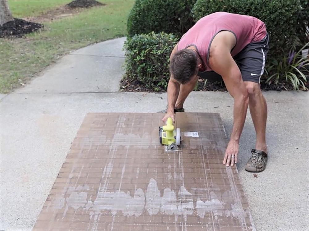 A man cuts down a brick board panel outside.