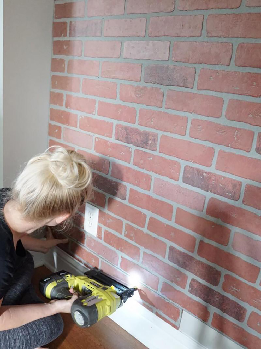 A woman attaches a brick board panel to a wall.