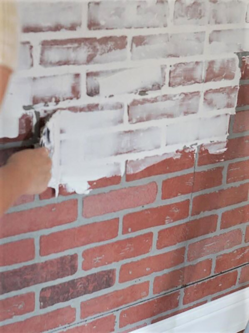 A person smears joint compound on a faux brick wall with a large putty knife.