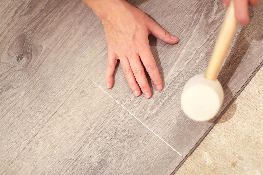 A person installing click lock vinyl flooring over a plywood subfloor.