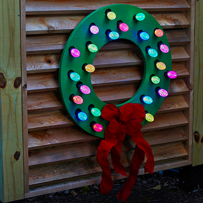 A DIY wood wreath with colorful lights and a red bow.