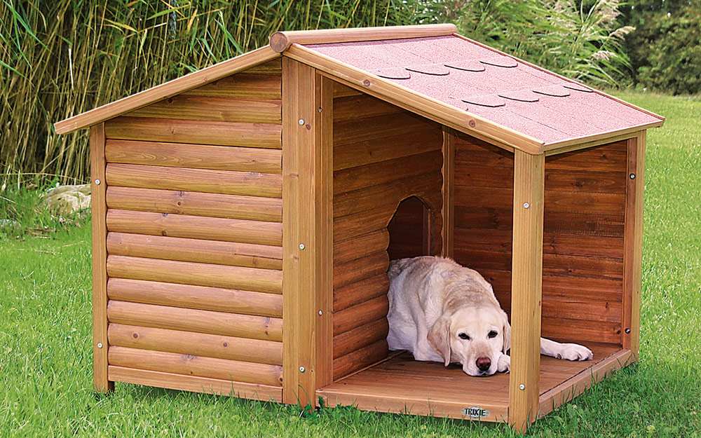 A dog resting on the covered porch of a dog house.