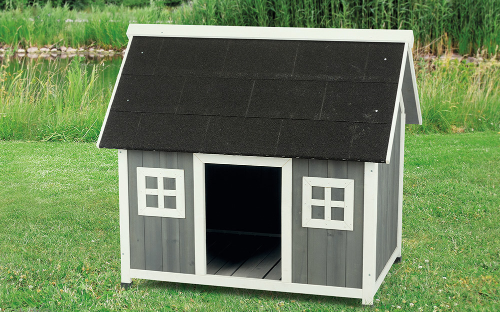 A dog house with faux windows and a shingled roof.