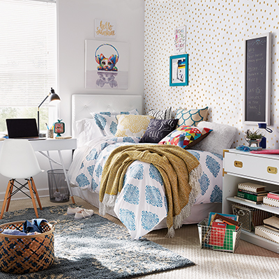 Dorm room with a bed, bedside table, lamp, wall art and storage unit.
