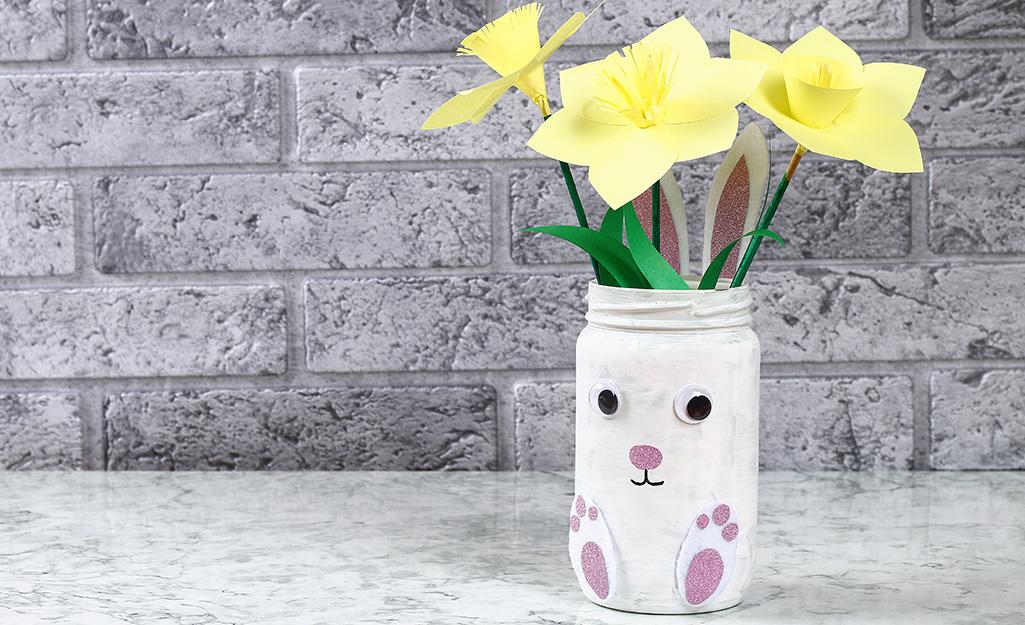 Một chiếc lọ Mason được làm để trông giống như một chú thỏ trắng đang cắm hoa.