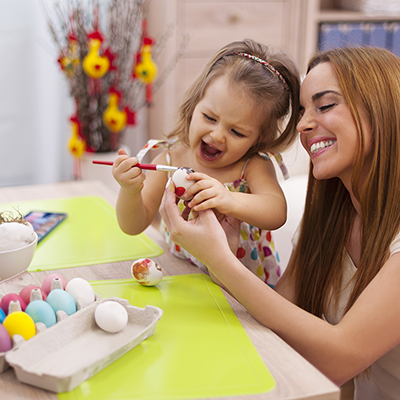A mom and young daughter decorate eggs for Easter.
