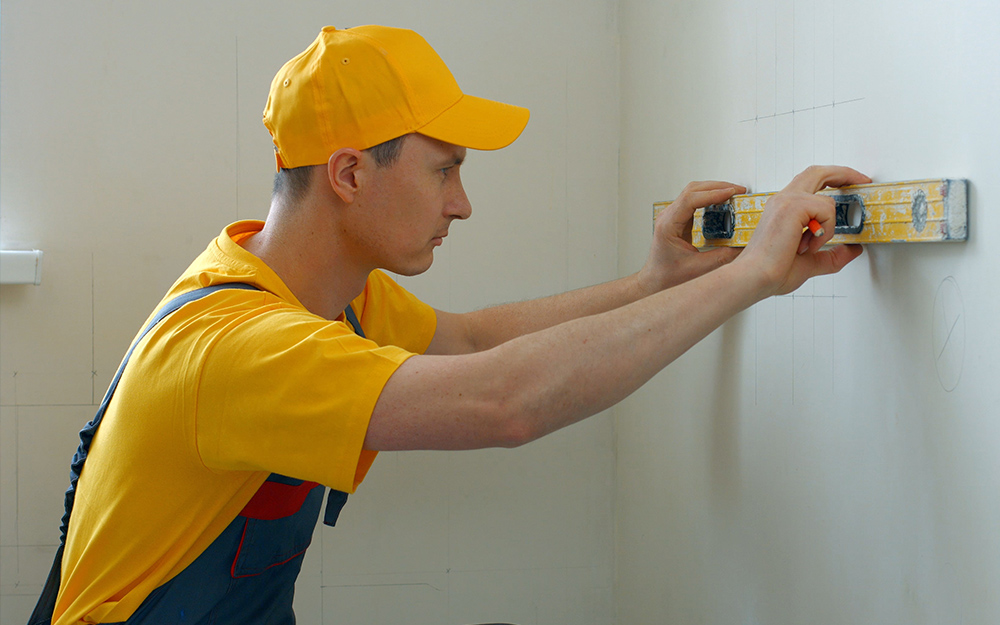 A man uses a level on a wall.