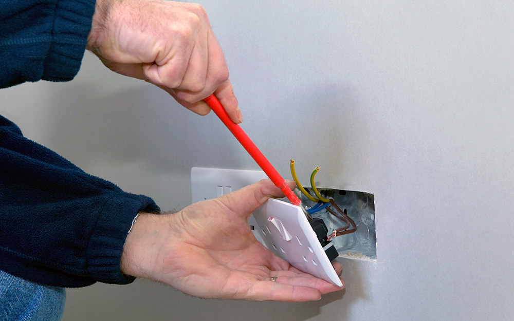 Person removes an outlet cover.