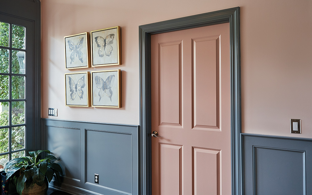 A hallway with finished wainscoting painted a deep shade of green.