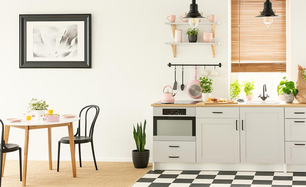 Sàn ô vuông cộng với tác phẩm nghệ thuật đen trắng trong một nhà bếp đơn giản.