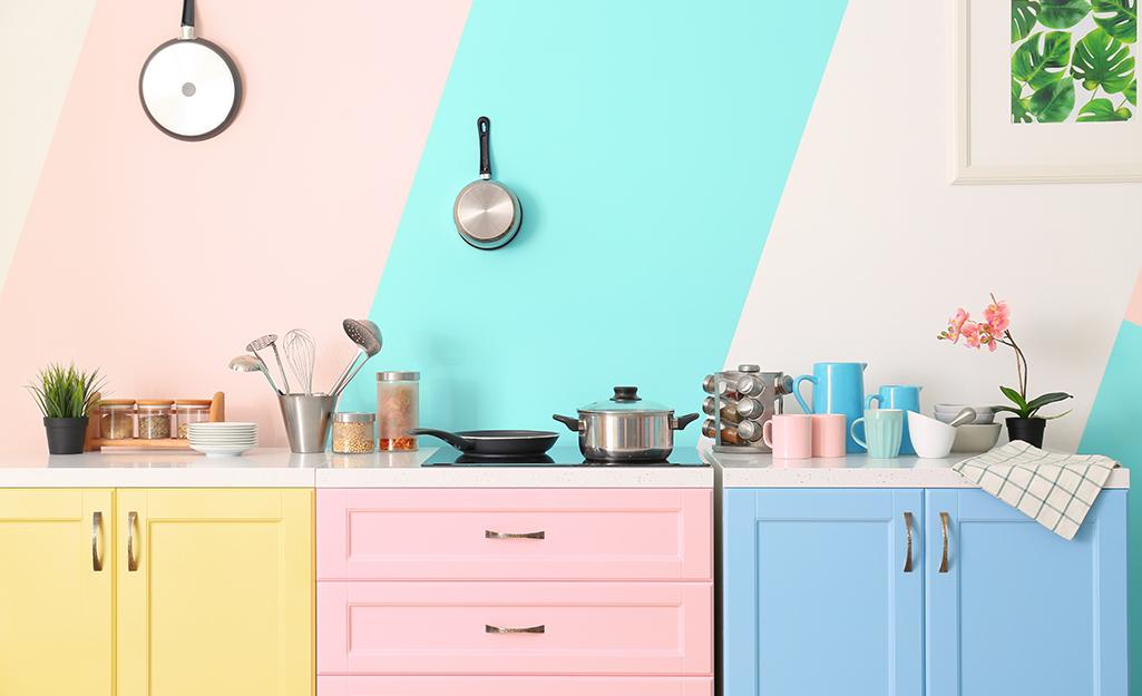 Tủ bếp nhiều màu sắc vàng, hồng và xanh dương trên nền tường có sọc xanh.