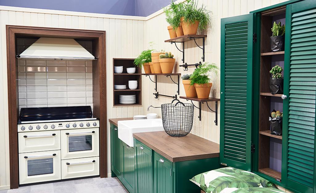 Những chậu trồng cây với các loại thảo mộc khác nhau được đặt trên kệ treo trong nhà bếp màu trắng và xanh lá cây.