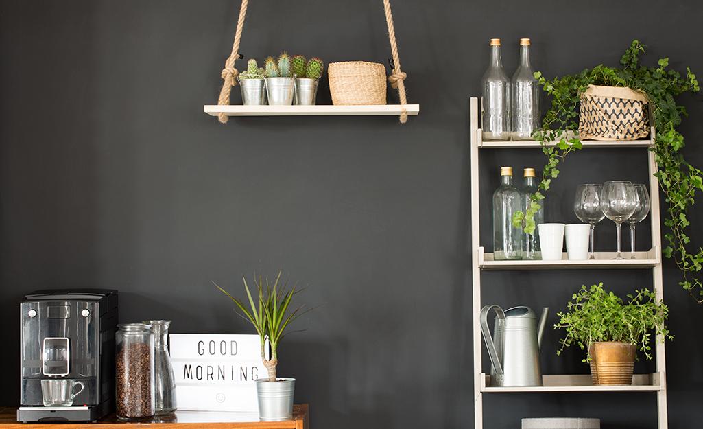 Kệ treo và giá đỡ dựa vào tường bếp màu đen.
