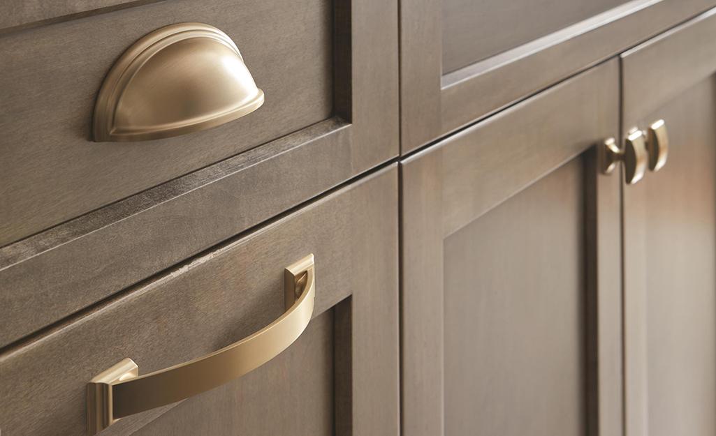 Phần cứng màu bạc được đánh bóng đặt trên tủ bếp màu xám.