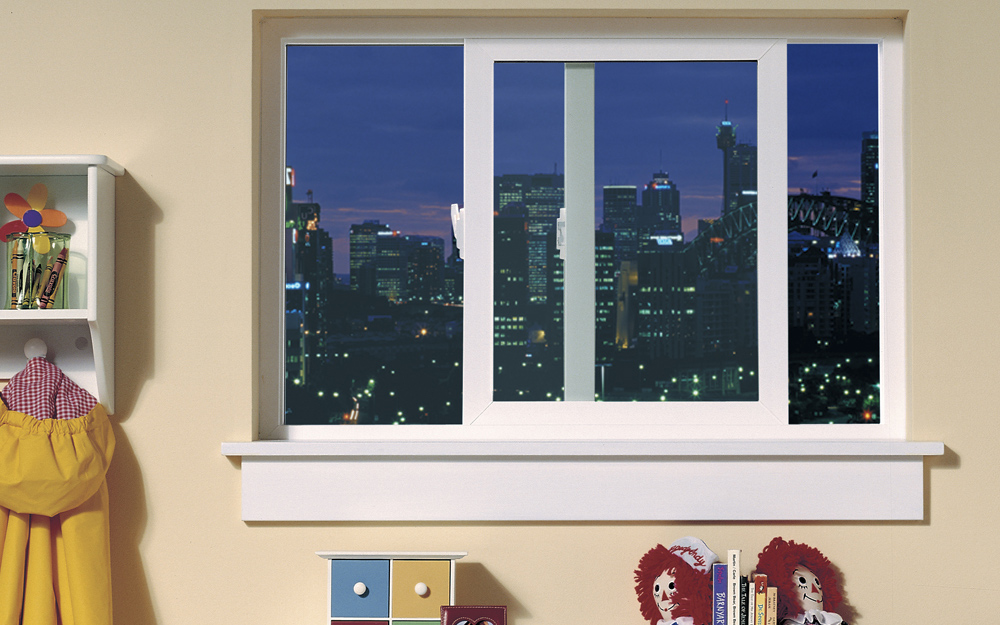 A sliding egress window in a child's room has a view of a city skyline.