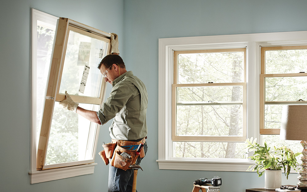 A person installs an egress window in a room.