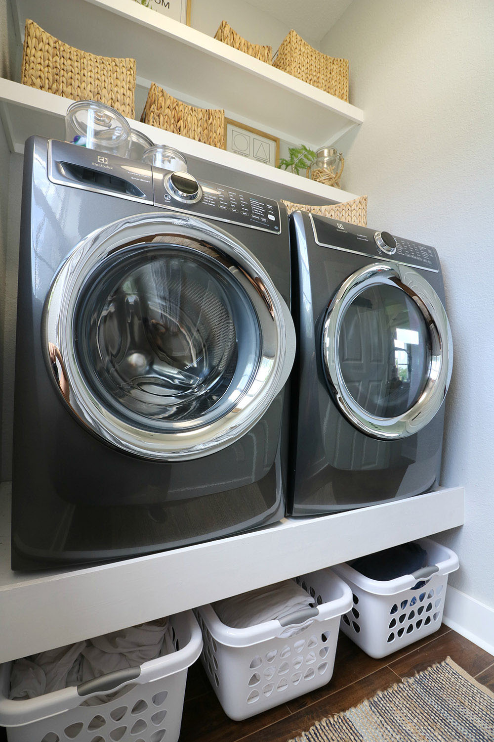 A laundry room with storage above and below a front load washer and dryer.