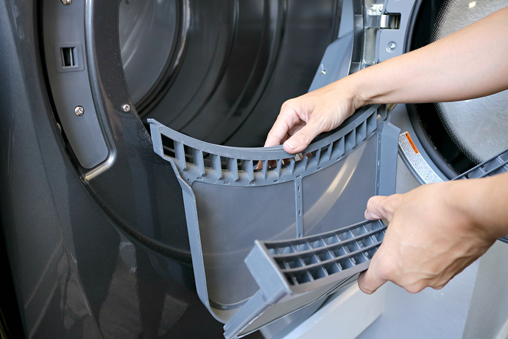A person opening the lint screen that has been pulled out of a dryer.
