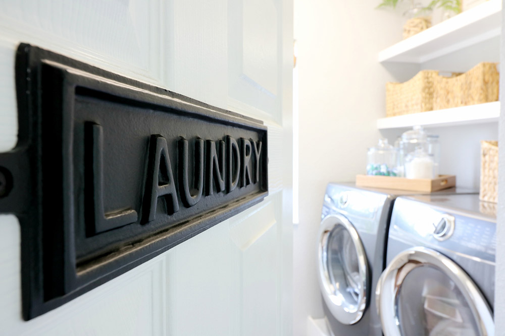 A black laundry sign on a white door.
