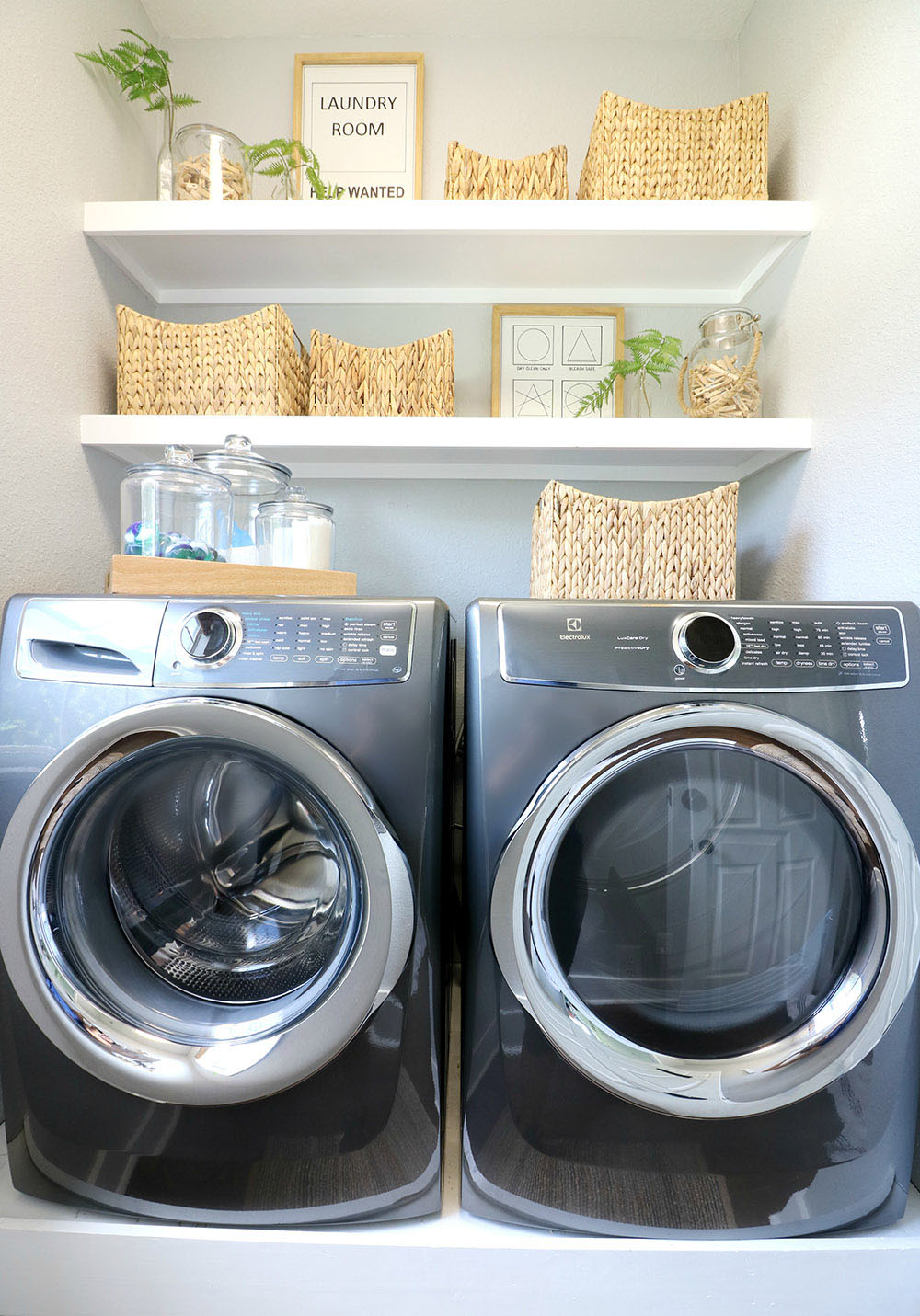 A laundry room with open shelving and the Electrolux Smart Boost Technology washer and dryer.