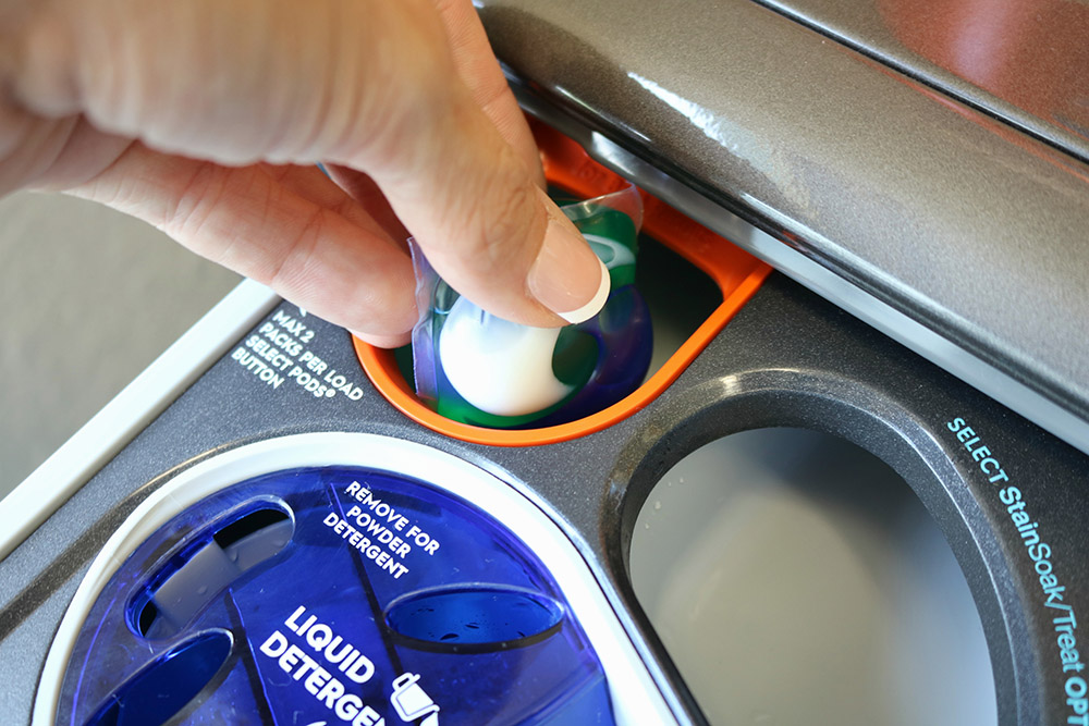 A person placing a laundry pod inside an Electrolux Smart Boost Technology washer.