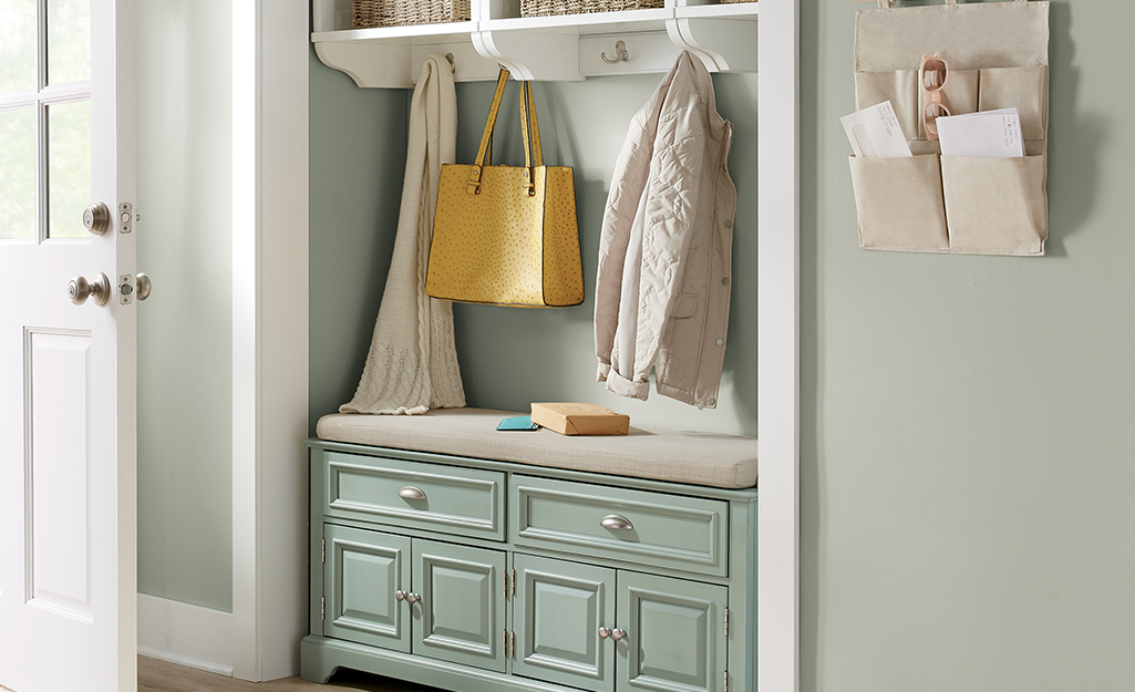 Hall tree with green drawers and white shelves.