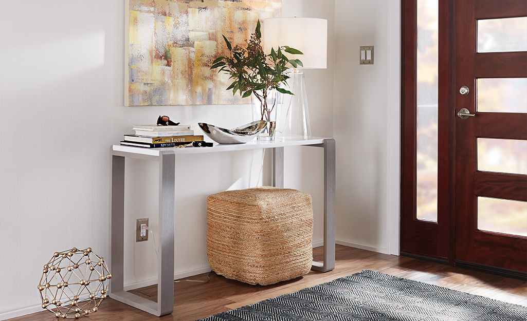 Small metal hallway table with a large storage basket.
