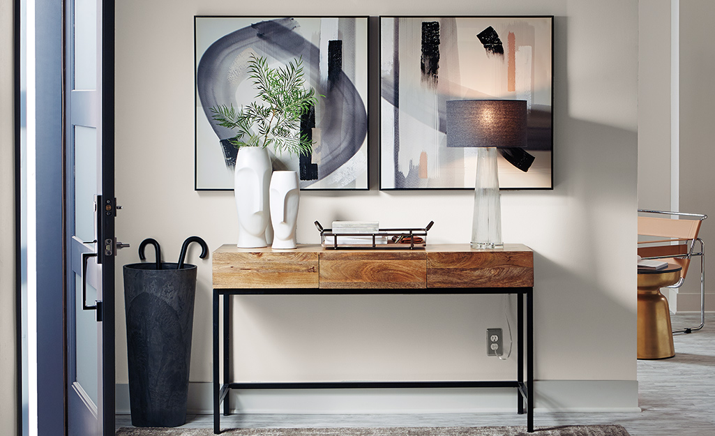 Small console table next to door with white vases.