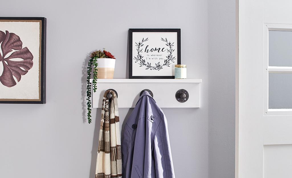 Wall shelf beside door with hooks for hanging coats.