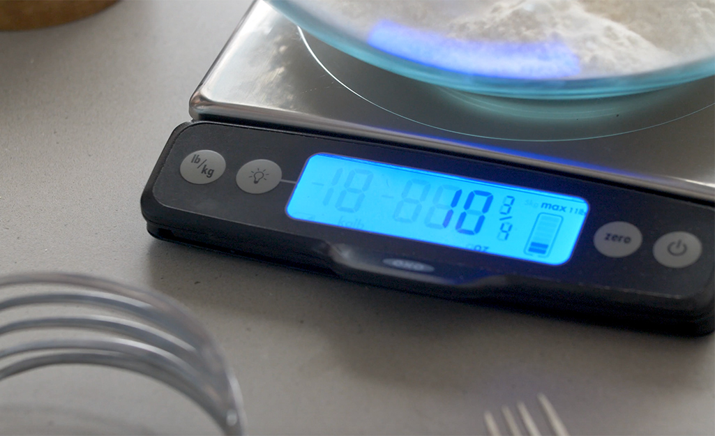 Flour in a glass mixing bowl being weighed on a digital scale