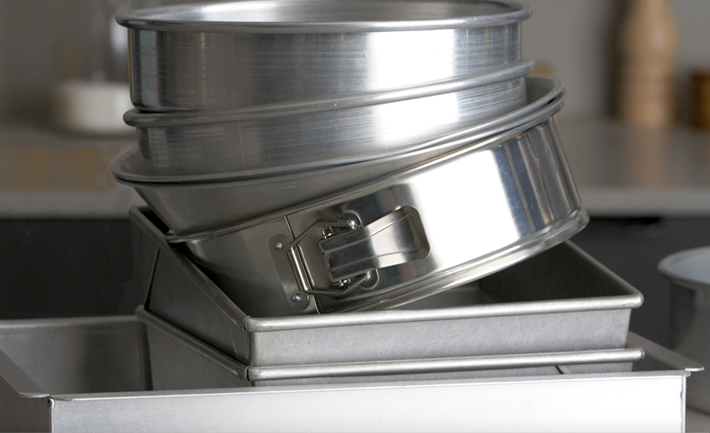 A stack of circular silver cake pans placed on top of square baking pans