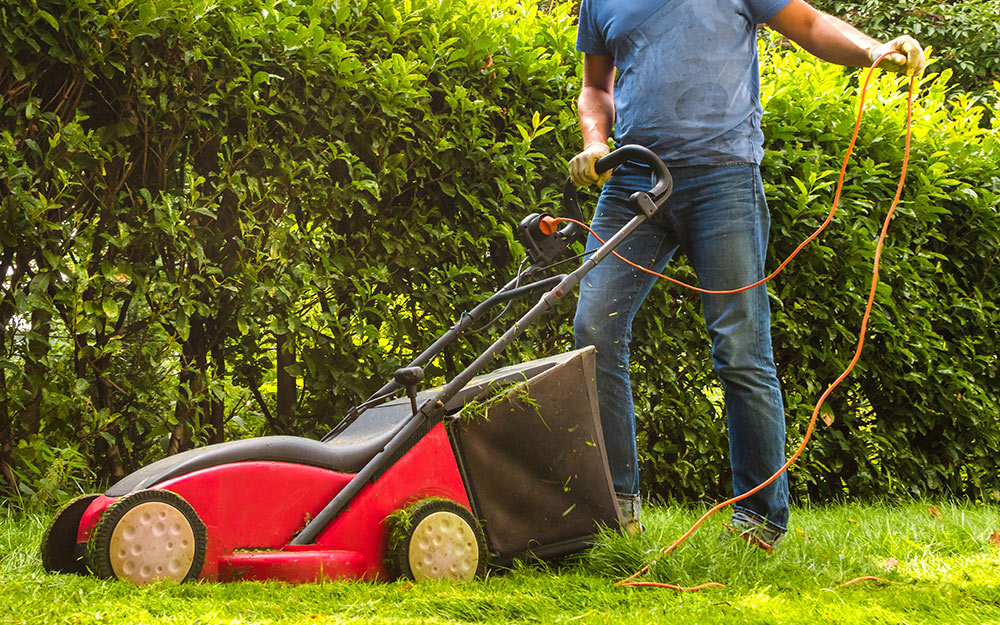 A person pushing a lawn mower attached to an extension cord.