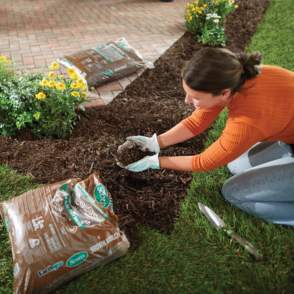 Woman placing a handful of mulch in her flowerbed.