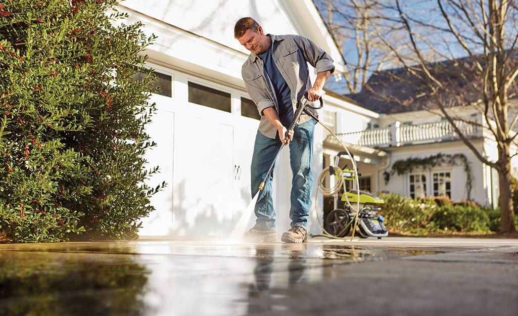 A man pressure washing his driveway.