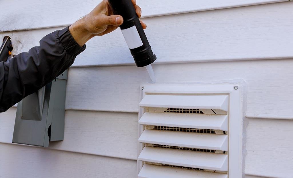 A person sealing a vent with caulk.