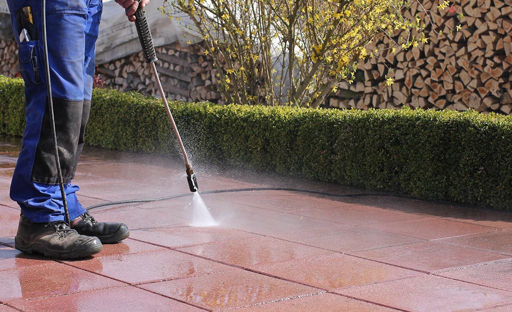 Homeowner pressure washing patio