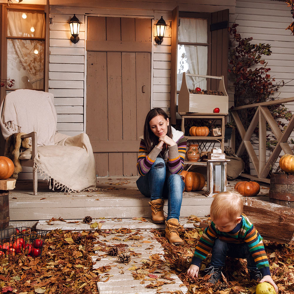 A woman and child sitting on the front porch with fall decorations.