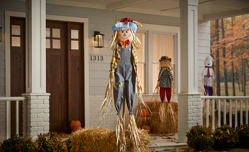 A scarecrow and bales of hay on a front porch.