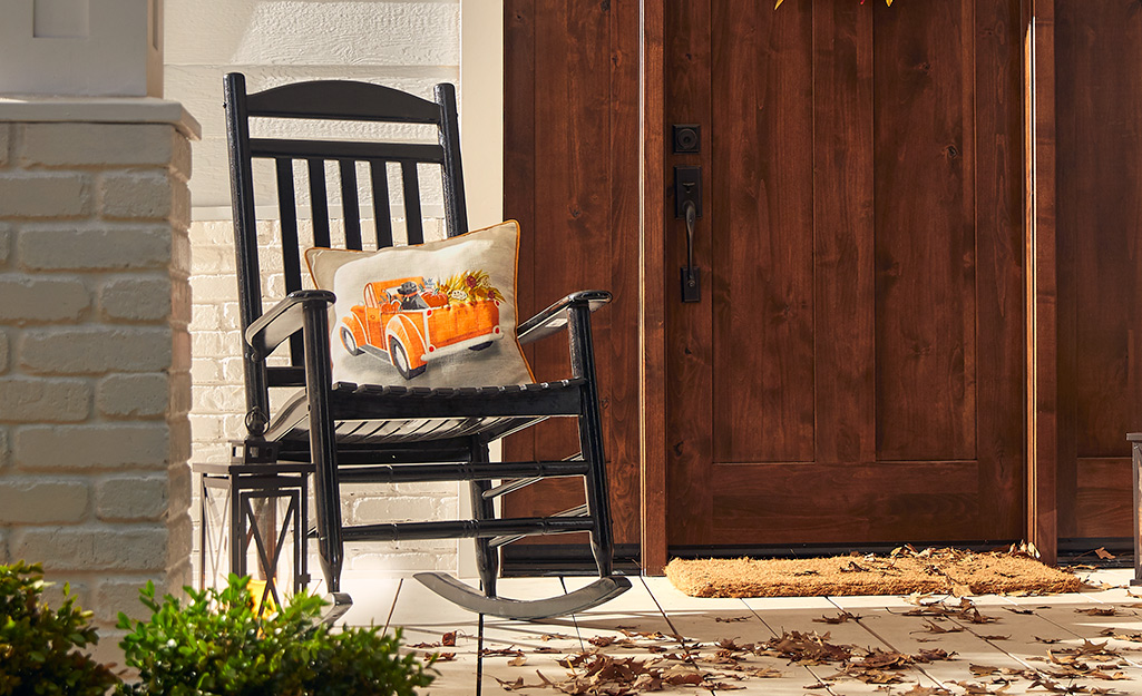 A rocking chair and fall pillow on porch.