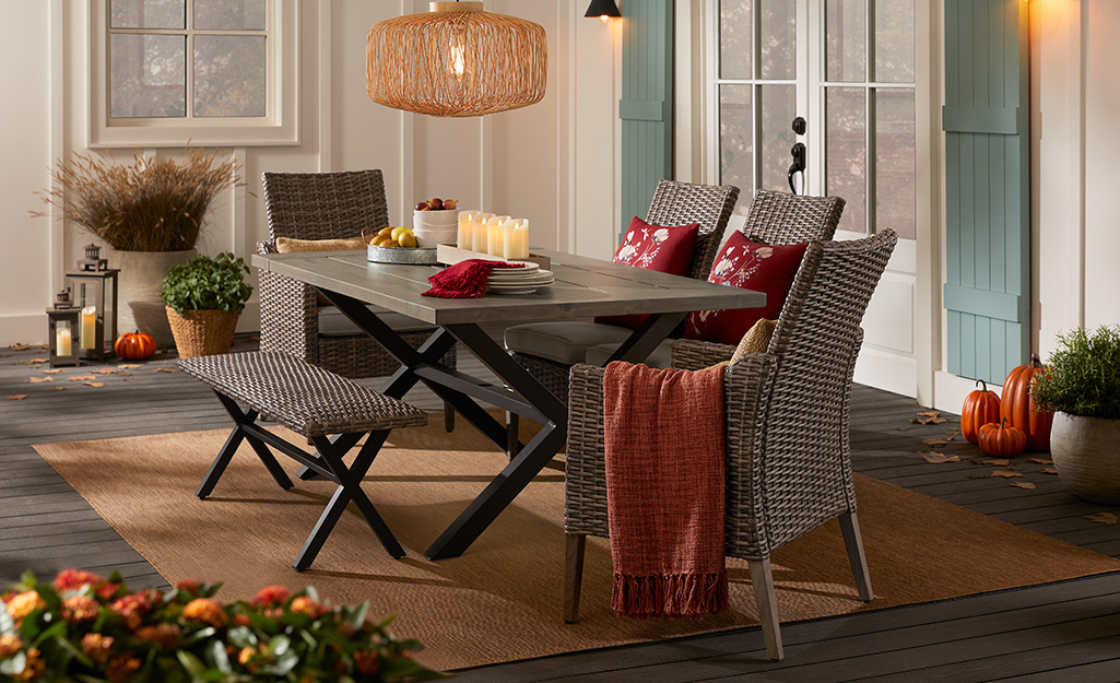 A dining room set on the back porch with fall decorations.