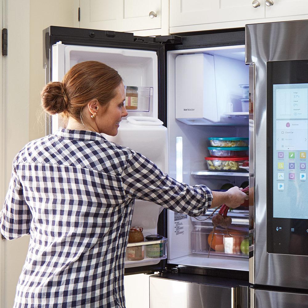 A woman opening a refrigerator door.