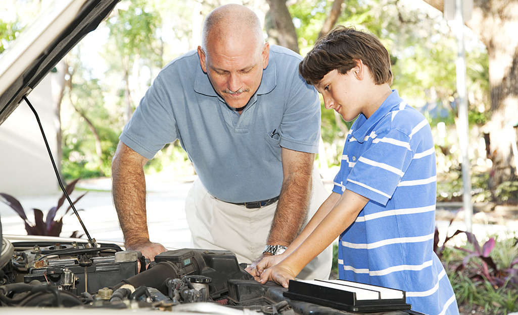 A father and son working on a car engine.