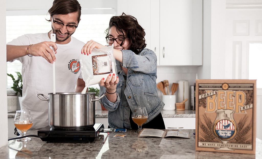 A couple uses a home brewing kit.