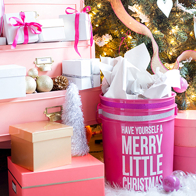 A group of pink, white, and gold presents sitting under a Christmas tree.