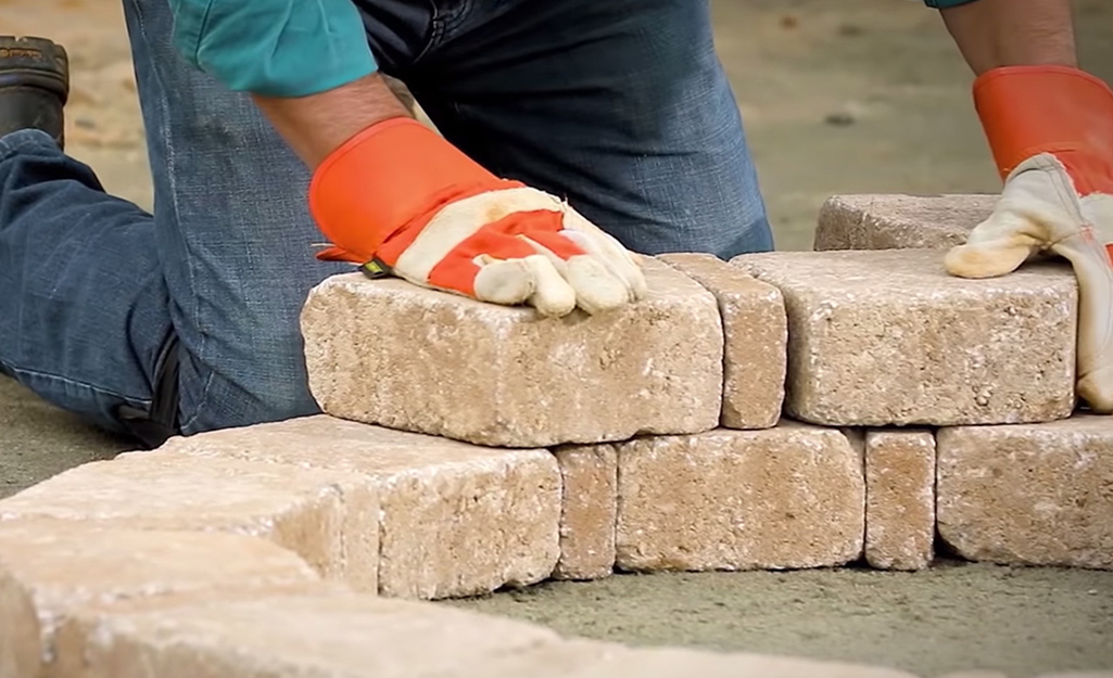A person using pavers to build a fire pit.