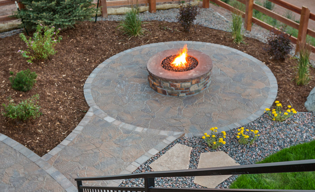 Stone fire pit on a round patio bordered by plants and shrubbery.